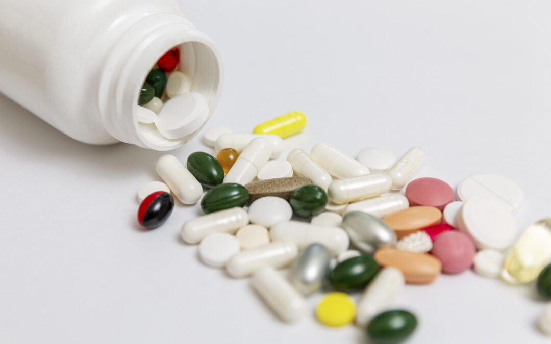 multi-colored-pills-spilled-out-white-bottle-onto-table-medicine-close-up-space-text