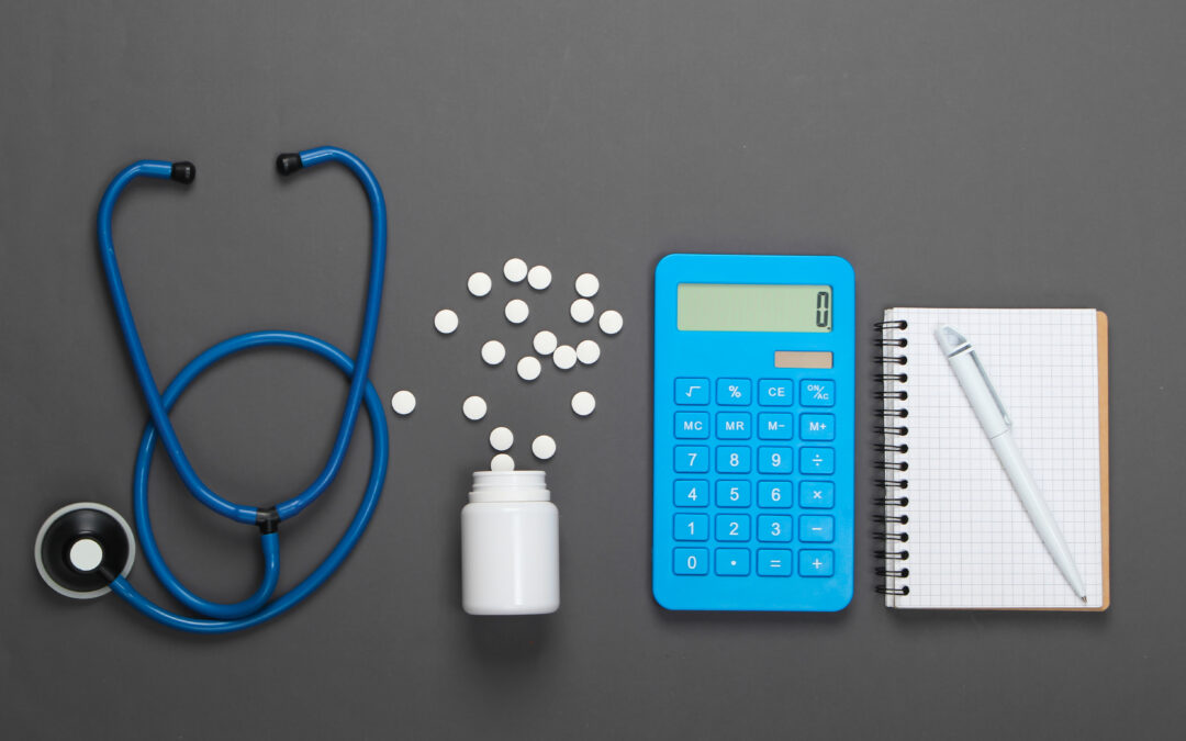 Health Care Concept. Calculator with a stethoscope, pills, notebook on gray background. Top view